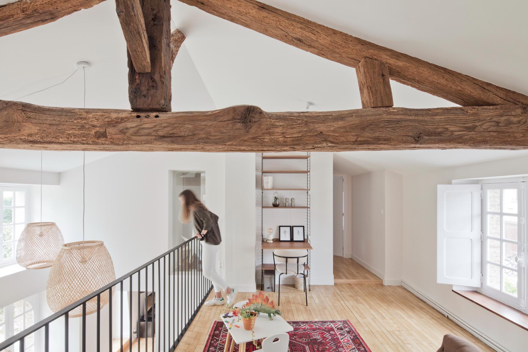 Réhabilitation d'une maison par une agence d'architecture, avec des poutres anciennes apparentes et un garde corps en fer noir