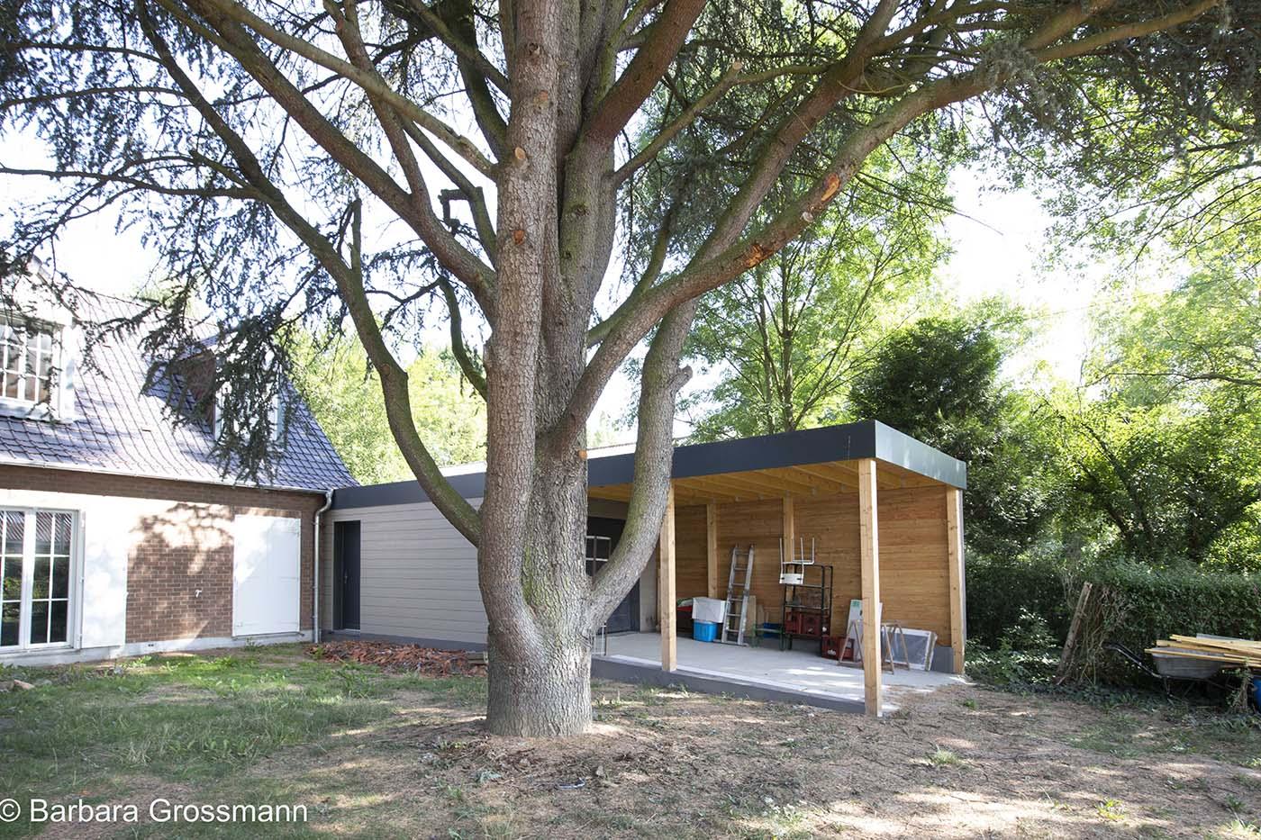 Atelier et carport devant la maison, pour garer une voiture, stocker du bois et ranger le matériel de jardin